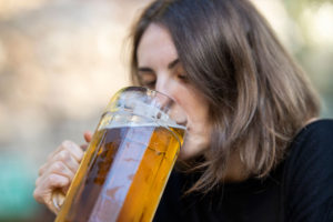 woman drinking big glass of alcohol might increase the risk of early wrinkles, dark eye and eye bags