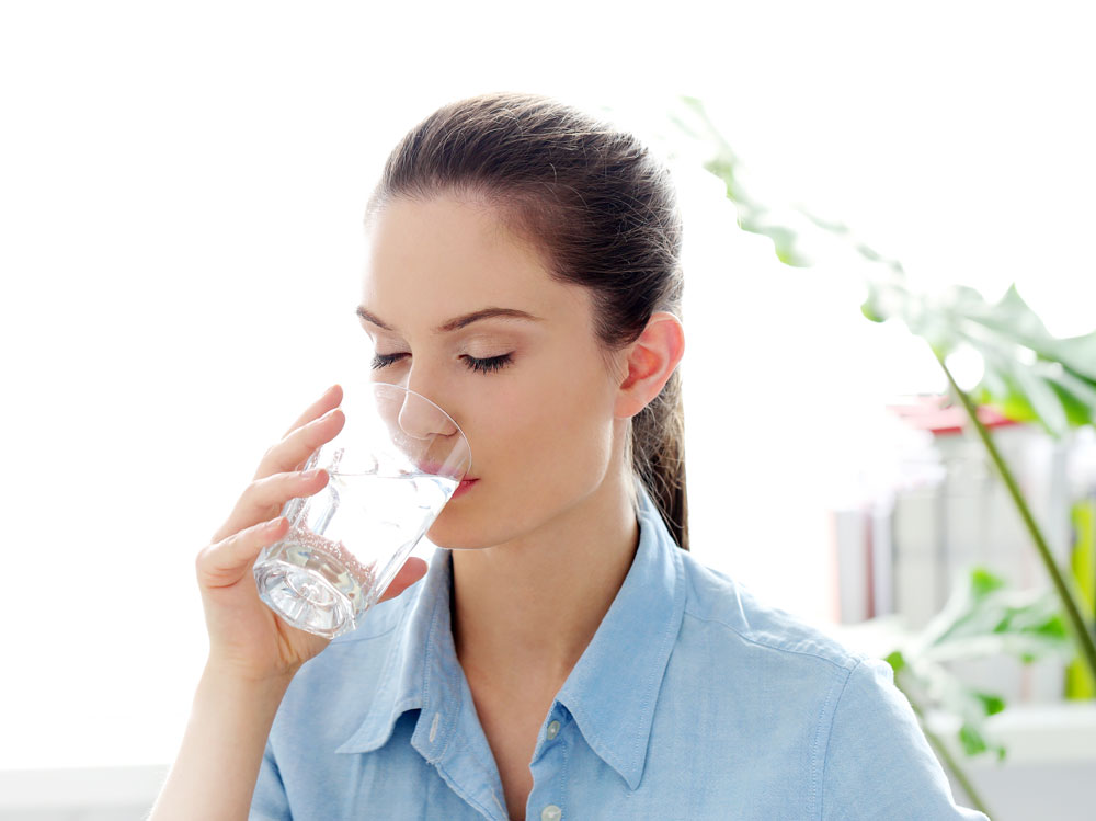 woman drinking water to promote healthy and radiant skin