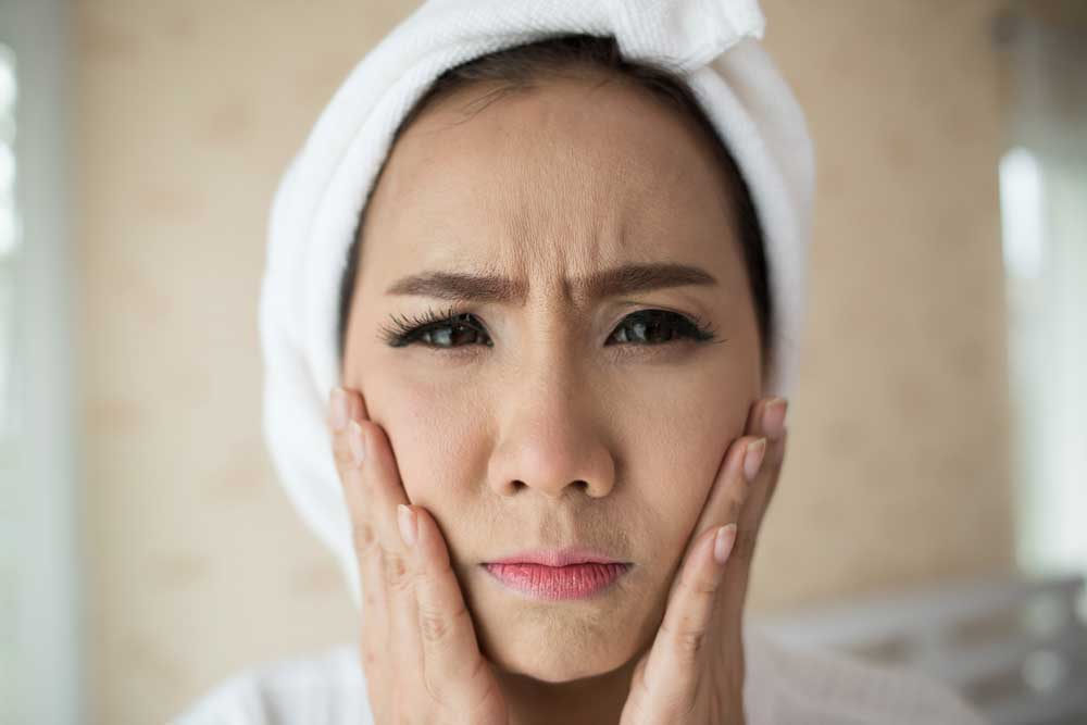 asian woman worried about dark eye circle and eyebags in the morning