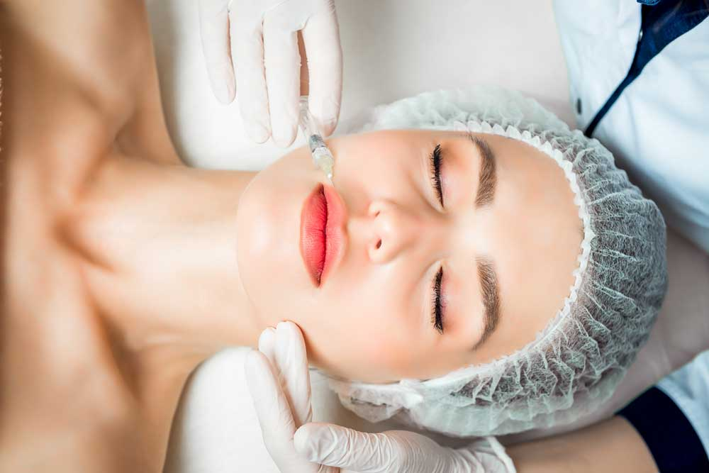 woman undergoing dermal filler treatment to fight off wrinkles around the mouth