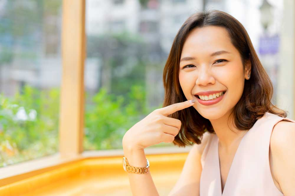 asian woman showing healthy teeth